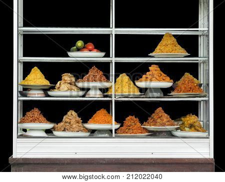 shelves with various indonesian dishes in black back