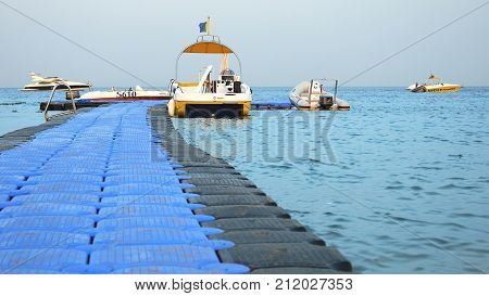 Sharm-El-Sheikh, Egypt - August 27, 2017: Powerboats and touristic ship are moored at the floating jetty dock at the tropical resort beach at sunset. Seaside area for vacation and summer relaxation.