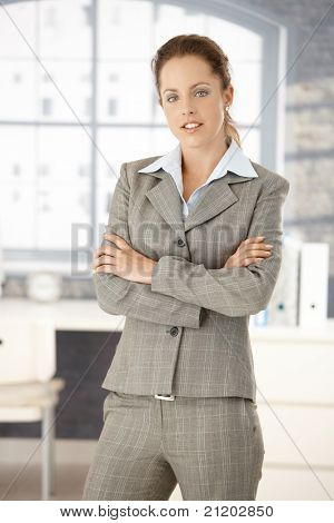 Young attractive woman standing in office front of window, arms crossed.?