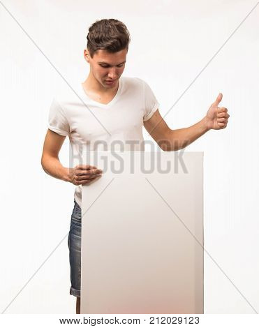 Young wistful man portrait of a confident businessman showing presentation, pointing paper placard gray background. Ideal for banners, registration forms, presentation, landings, presenting concept.