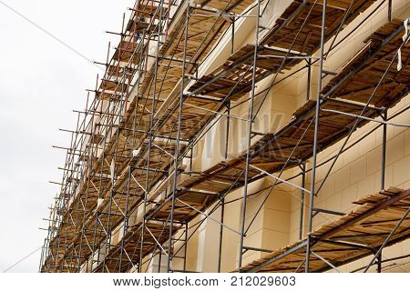 Metal Scaffolding With Wooden Decking Built Around A Historic Building For Restoration Work And Reno