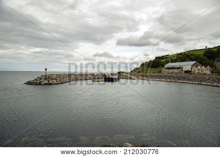a harbour with barge docked and moody sky