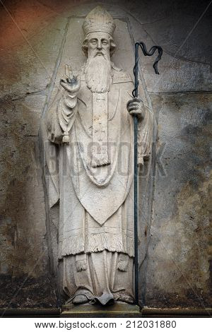 A rustic looking image of st.patrick in stone