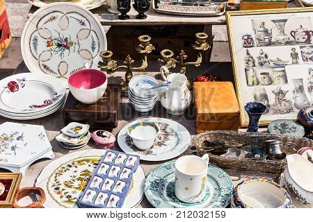 Paris France - Jule 09 2017: Old vintage objects and furniture: candle holders plates vessels vases teapots cups at a garage sale at the flea market in Paris.