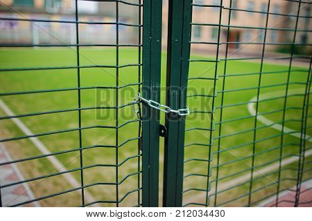 Close Up Metallic Net-shaped Green Fence That Closed And Wrapped By Chain On A Background Of School