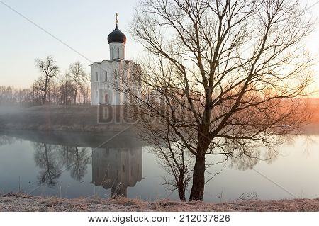 A Misty Lake With A Boat In Front Of The Church In The Early Spring At Dawn