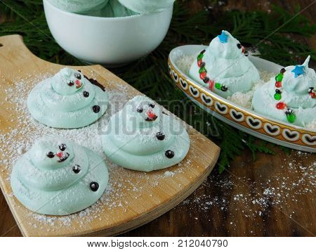 Funny snowmen formed of mint homemade marshmallow (zephyr) on a wooden board covered with sugar powder