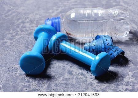 Workout and measurement concept. Dumbbells in cyan color water bottle and measuring tape on grey texture background. Sports and health idea. Water and measure tape near plastic barbells close up
