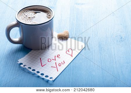 Morning coffee and love you message - Hot coffee in an antique cup heart shaped sugar and a piece math paper with the words love you on it on a blue background under morning light.