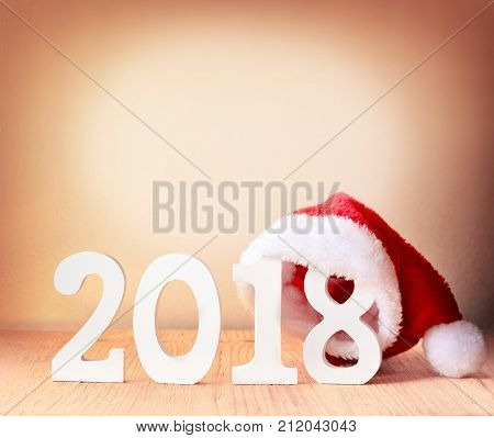 santa fur cap on a rustic wooden background with figures 2018