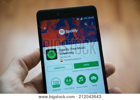 Los Angeles, november 2, 2017: Man hand holding smartphone with Spotify application in google play store