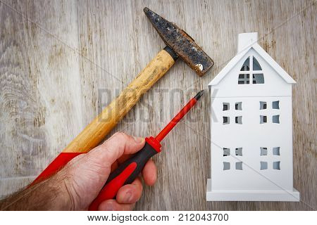 Repair and reconstruction of house concept. hammer screwdriver in hand of builder and model of house on wooden background. Construction work in the house