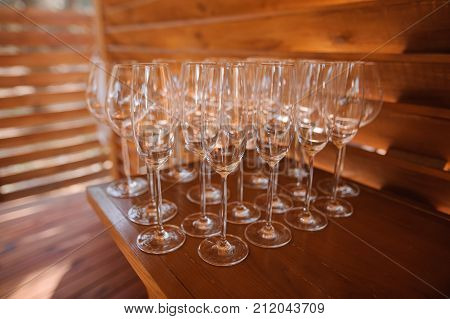 Set of washed and clean glasses for alcoholic drink arranged on the small wooden table