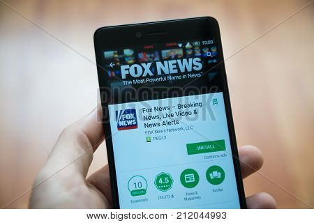 Los Angeles, november 2, 2017: Man hand holding smartphone with Fox News application in google play store
