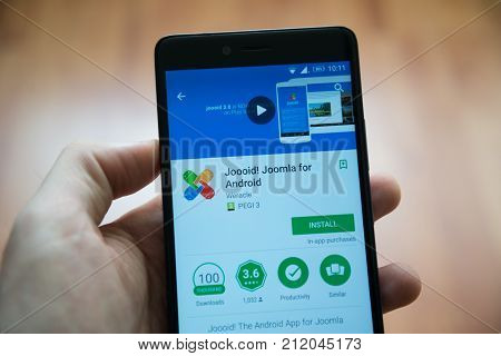 Los Angeles, november 2, 2017: Man hand holding smartphone with Joooid, Joomla for android application in google play store