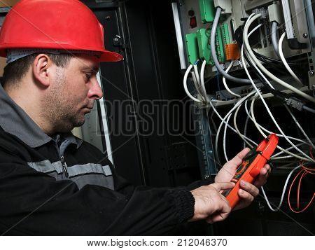 Worker in red helmet make electrical measurements