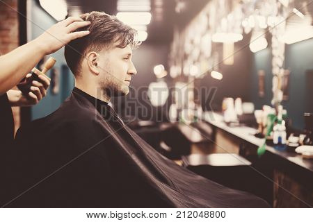 Barber shear hair electric car to a young guy hipper hair for a fashionable hairstyle. Concept hair salon barbershop.