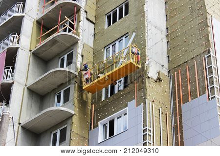 work with yellow front suspended cradle on a newly built high-rise building.