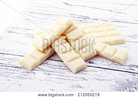 white chocolate bars and white choco pieces on wood