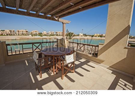 Terrace Balcony With Chairs And Table At Tropical Luxury Apartment