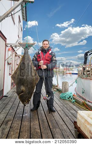 Fisherman on the pier with a big fish. halibut.
