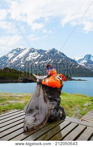 Man fisherman with huge fish Halibut. Behind the beautiful landscape.