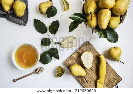 pears on a table on a white background next to a cup of honey and a cutting board and a knife