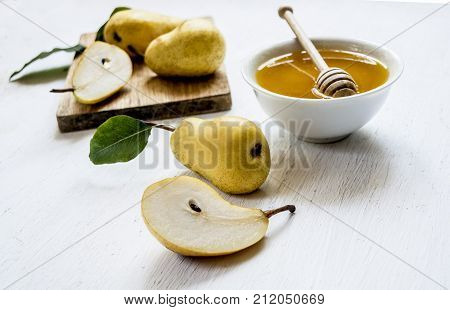 pears and a piano with honey on a table white