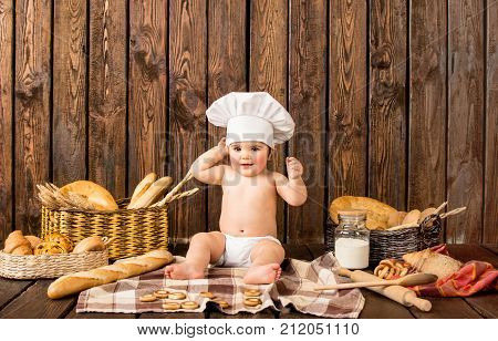 little girl in a cook costume among a baking bread rolls of flour confectionery on a brown wooden floor sits on a wooden background background