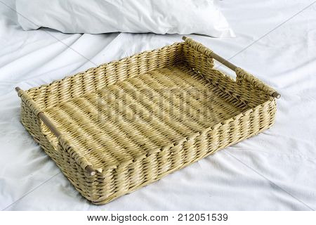 wicker basket made from a vine stands on a white bed