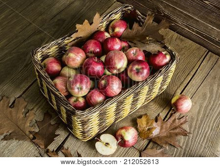 wicker basket with apples on a wooden table