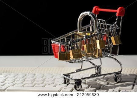 A trolley on computer keyboard with padlocks / Security of online shopping concept