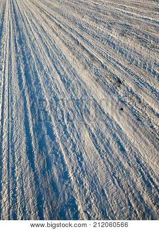 compacted to a solid state and ice snow on the road, winter close-up photo