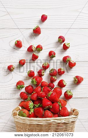 Strawberry explosion. Photo of strawberry in basket on white wooden table. Top view. High resolution product.
