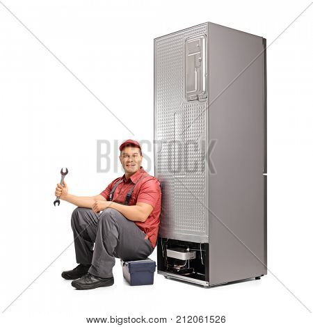 Repairman with a wrench sitting on a toolbox and leaning against a fridge isolated on white background