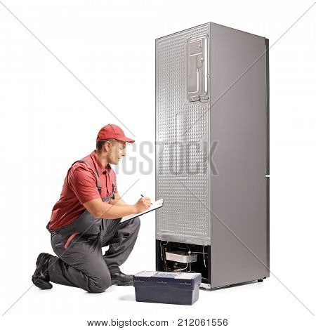 Repairman kneeling behind a fridge and writing in a clipboard isolated on white background
