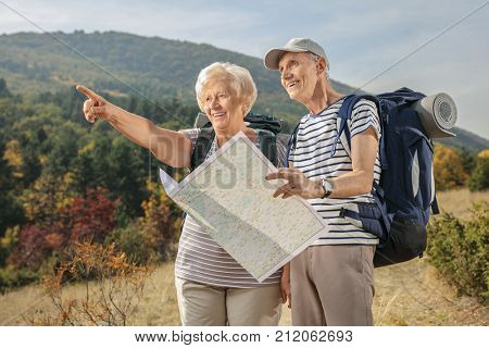 Elderly hikers holding a generic map and pointing outdoors