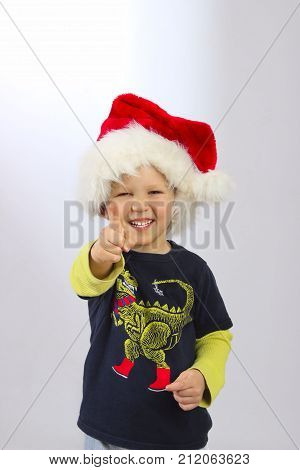 Holidays, Christmas, people, children concept - happy smiling little boy in Santa helper hat. Smiling little boy wearing on red Santa helper hat, cropped shot.