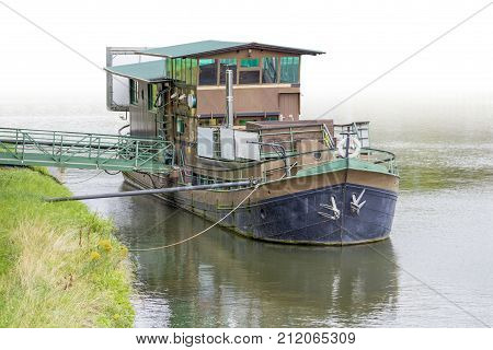 riparian scenery showing a anchoring old house boat with bridge on water surface