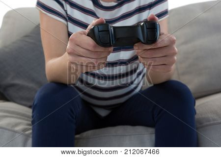 Mid section of woman playing video game on sofa