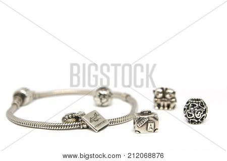 Heart, globe, kitties, journey and suitcase. Silver beads and charms bracelets isolated white background. I love Paris passport. Photo of Macro shot of jewelry.