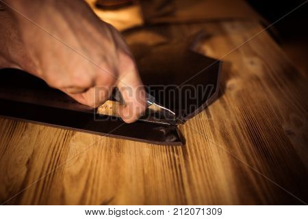 Working process of the leather belt in the leather workshop. Man holding crafting tool and working. Tanner in old tannery. Wooden table background. Close up man arm.