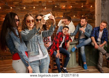 Acquaintance and flirtation. A woman and a group of men. Friends discuss the girl