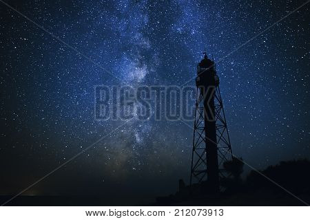 Silhouettes Of The Old Lighthouse Sandy Beach And Ocean Against The Background Of The Starry Sky