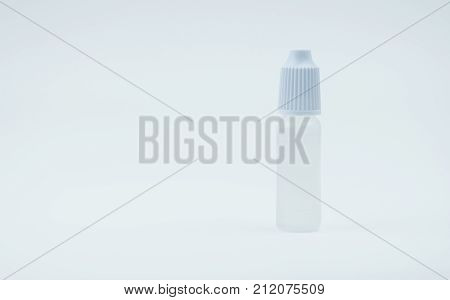 Eye drops bottle with white cap on white background with blank label and copy space just add your own text. Dry eye disease from smartphone use digital screen. digital eye strain.