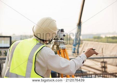 Surveyor builder Engineer with theodolite transit equipment at construction site outdoors during surveying work