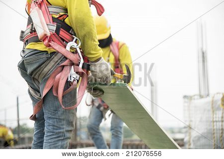 Carpenter's tool belt with hammers at construction site