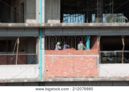blur of female worker bricklayer laying brick a wall construction in industrial building site poster