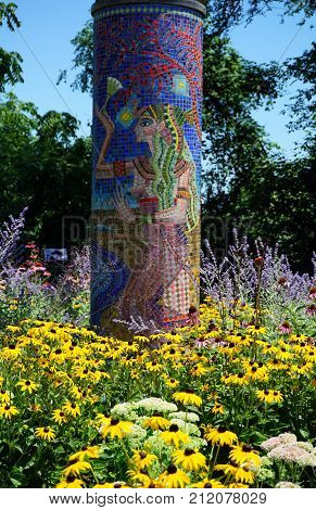 JOLIET, ILLINOIS / UNITED STATES - JULY 25, 2017: A mosaic column pedestal, created by Andrea Rountree, and illustrating the ancient Egyptian story of Isis and Osiris, stands in the midst of a flower garden, in the Route 66 Park.
