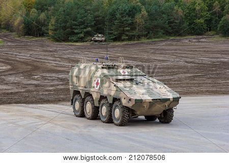 MUNSTER / GERMANY - OCTOBER 9 2017: German GTK Boxer medic version from Kmw and Rheinmetall stands on a platform near battlefield